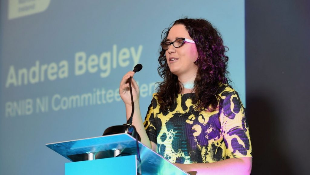Photo of Andrea Begley speaking at the podium at an RNIB event